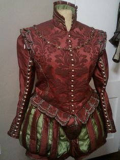 Elizabethan gentleman's suit, in tomato red brocade, accented and lined with lime green silk, and detailed with antique gold braids and brushed brass buttons. The buttons on the sleeves are functional.