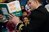 150302-N-GW695-005  NEW YORK (Mar. 2, 2015) Lt. Matthew Stroup, from Romeo, Mich., deputy director of the Navy Office of Information East, reads Hop on Pop by Dr. Seuss to a classroom of students at Public School (PS) 195. The National Education Association's Read Across America event is an annual reading motivation and awareness program that calls for every child in every community across the country to celebrate reading on March 2, the birthday of children's author Dr. Seuss. (U.S. Navy…