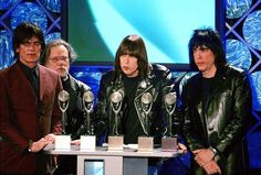 On March 18, 2002 the Ramones were inducted into the Rock and Roll Hall of Fame. Dee Dee, Tommy, Johnny and Marky. Sadly, Joey is missing from the photo because he diedof lymphoma the year before, and Dee Dee died only a couple months after this photo was taken from a heroin overdose. Additionally, Marky is pictured, who was not one of the founding members, he joined the band in 1978.