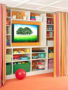 If you don't have built ins already, add shelves / bookcases but leave a box frame area for tv. Add a curtain rod (hanging from ceiling hooks, if walls are not narrow enough) add the curtains. Ideal for playroom, den or close off space for bedroom. G;)