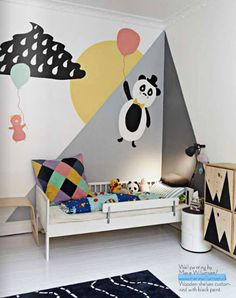 Comme pour faire office de ciel de lit dans cette chambre de garçon, les murs autour du lit s'animent d'une fresque à la fois graphique et ludique.