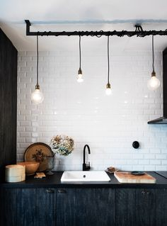 lightbulbs hanging from pipe in kitchen with white subway tile