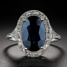 Antique Sapphire, Platinum and Diamond Ring, A deep, dark and mysterious midnight-blue oval sapphire, weighing 3.50 carats, is enshrined in a masterfully handcrafted platinum and diamond mounting dating from the Edwardian/early-Art Deco design period – circa 1910~early 1920s.