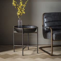 Wesley Side Table  This unusual side table features a metal cross bar stand that holds a deep hammered textured tray in a black finish with gold edge detailing.