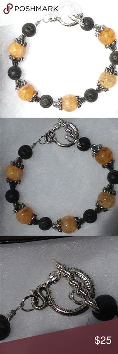 """Yellow Dragon's Vein Agate Lava Rock Bracelet This unique bracelet is made with natural dragon's vein agate and black lava rocks. The silver tone snake toggle clasp adds a unique touch! This piece measures 7.5"""" long.   You can use this piece as an oil diffuser! Just add one drop of oil to a couple of the lava rocks. The effect will last up to a couple of days.   All PeaceFrog jewelry items are handmade by me! Take a look through my boutique for coordinating jewelry and more unique creations…"""