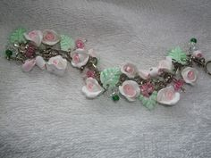 Pink rosebud, bead and green leaf charm bracelet.   #handmade #CreatingCottage #Roses #CottageStyle #Cottage #ShabbyChic #Shabby #Chic #polymerclay #white #pink #romantic  @Renee Holtzer