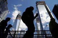 Visitors to the National September 11 Memorial walk below the rising towers 1 World Trade Center, left, and 4 World Trade Center, Monday, Sept. 10, 2012 in New York. Photo: Mark Lennihan / Associated Press