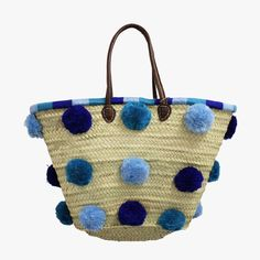 Our chic Grande Marrakech Blue Melange Tote from Soeur du Maroc is handmade from woven palm leaves, wool pom moms and leather handles. Accented with turquoise, cobalt and sky blue pom poms, this playful tote is perfect for a trip to the farmers market, a day at the beach or as an everyday carryall.