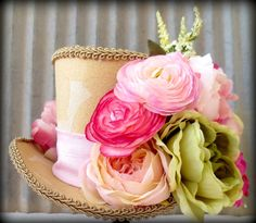 This hat features a gold tone textured fabric. The Sash a dreamy pink. The flowers are a flourish on the side.    It measures 5 1/2 high by 7 x 8 wide
