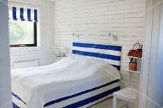 Bedroom with white wood paneling and double bed with cover, head board and blind with a blue and white design
