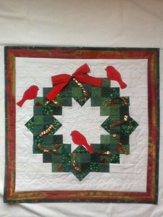 Quilted Christmas Wreath,Braided Rick Rack Ribbon, Red Birds. A fun wreath to make with a variety of green squares and flying geese blocks. I braided red and gold lame rick rack together and inserted the ends in the seam allowances to give the impression of the ribbon flowing around the wreath. I added three red birds and of course a  red bow.  In this wallhanging I tried a new technique of mitering the inner border.  I can make a Keepsake Quilt for you.  Email to…