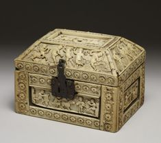 finely carved ivory casket is decorated with curly-haired cupids in the guise of warriors, dancers, and musicians. bone  ivory on wood. 10th century