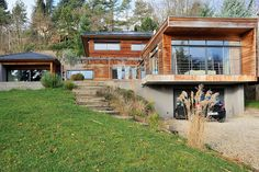 Coincée au fond d'un terrain triangulaire exigu et pentu, cette maison s'isole du voisinage tout en s'ouvrant sur sa terrasse et la piscine. Le contraste entre l'anthracite (murs soutènement, tuiles, menuiseries et stores) et le bardage de cèdre rouge met en valeur la volumétrie et la modernité de l'architecture, souligne l'horizontalité et la chaleur de