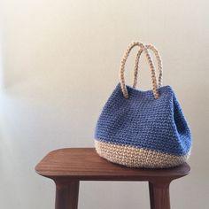 ナチュラルカラーのしっかりした麻ひもと、ブルーの軽く柔らかな麻ひもの2種類で編んだバッグです。ふっくらまるいバケツ型をキュッと絞ると、ころんとしたかわいいフォ...