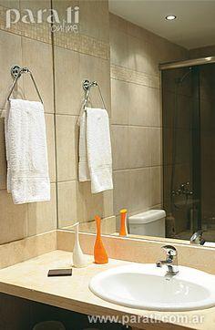 El baño, revestido en <i>porcellanato</i> color maíz, lleva un espejo pegado a filo, mesada de <i>Corian</i>, bacha oval embutida (<i>Ferrum</i>) y grifería monocomando (modelo <i>Swing</i>, de FV).