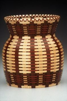 """LINCOLN SEITZMAN -- """"Petrified Cherokee Basket"""" 1999 12"""" x 10"""" [Ivorywood, Bloodwood, Ipe, Ink -- $8000]. This is not a basket, but an """"illusion in wood"""". Seizman, now retired, used basketry as inspiration for his pieced and turned objects. They are notable, first, for high-level problem-solving; second, for his respect for the craft skills of other, often anonymous makers; and, third, for his finely honed understanding of fiber art."""