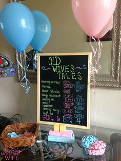 Love the set up of the entry table for The Vintage Modern Wife's gender reveal party using this old wives tales chalkboard, balloons, candy,and more!
