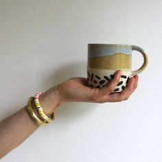 - White stoneware - Glazed with mustard,blue, and hand painted black marks- Small dip in handle for better grip- Made by hand, each mug will have unique markings and subtle color variationBY RECREATION CENTER * This ceramic item includes a shipping surcharge of $5