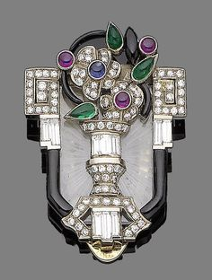 A ruby, emerald, sapphire, enamel and diamond clip brooch, circa 1930  The carved rock crystal plaque, with applied vase motif issuing a spray of flowers and leaves, set with circular and pear-shaped cabochon emeralds, rubies and a sapphire, and throughout with brilliant and baguette-cut diamonds, within a black enamel, surround, diamonds approx. 2.10cts total, length 4.8cm