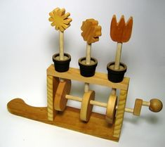 "Mechanical Toy - This kinetic toy was designed to be safe, entertaining, and stimulating for children. All components were hand-cut from wood or laser cut from medium-density fiberboard, then finished by sanding and oiling. Turning the crank causes the flowers to pop up and down in a seemingly arbitrary pattern. The flowers can all be removed and rearranged.   12"" x 14"" x 4"""