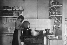Interiör från köket på Katarina västra barnkrubba med en kokerska som står vid vedspisen och lagar mat. - Stockholmskällan