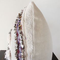 "Place of Origin: Co-crafted in Morocco & California  Material:  Front: Wool + Cotton + Sequins // Back: 100% Belgian Linen //  Down Fill  Dimensions: 28"" x 21""   Detail: Handira is the Moroccan name for what is commonly referred to as a  Wedding Blanket and is a traditional and"