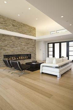 Horizontal lines of the fireplace, echoed in the ceiling, furniture, windows;  flooring (clear stained bamboo); stone wall