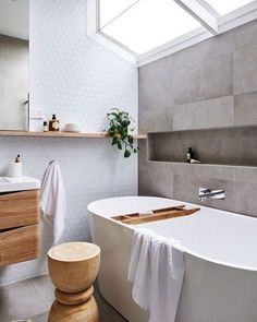 a serene Scandinavian bathroom with grey tiles, a white statement wall, much natural wood in decor and a skylight
