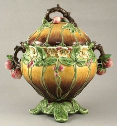 An Art Nouveau Julius Dressler Majolica tureen and cover, moulded with creeping wild strawberries against a mustard ground with rustic strawberry encrusted handle, tower mark.