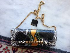 April 14, 2015 | GUCCI 1970 MULTICOLOR PYTHON TIGRETTE ACCORDION EVENING CHAIN BAG CLUTCH Gucci's spring collection for 2012 was a 1970′s-inspired glam fest, reflecting not only the rich color palette and silhouettes of the era but it's obsession with reflective surfaces, touches of art deco and a love of all things luxe and sinful to touch. Studio 54 was the scandalous benchmark of the era and so this impeccable collection from Frida Giannini