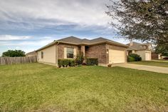 601 Wiley St., Hutto TX 78634 | GoodLife Realty | Spacious home sits on a large corner lot, offering tons of natural light and plenty of room to run, play and entertain. You won't miss a thing with this open floor plan offering easy access to the kitchen, dining and living areas. Home also features wood laminate flooring, a fireplace, garage entry keypad, double sink vanity in master bath, and a huge master bedroom. Roof replaced 2012!