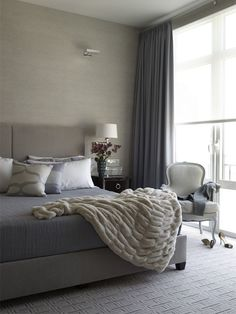 A wonderful collection of grey tones with small touches of dark wood furniture and an autumn tonedpadded headboard.