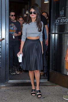 Selena Gomez wears a gray long-sleeved crop top, pleated leather Topshop skirt, Dior sunglasses and Kurt Geiger sandals