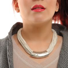 TICKTECH necklace made from glazed cord has a hammered metal feature tube at the front and hook fastening at the back. It's wonderful worn as part of both casual and occasion wear, whilst the silver colour of the tube itself is a fantastic contrast against the deep tones of the black, burgundy or natural versions of this cord necklace. Matching bracelets are also available.    Colours: Available in Black, Burgundy, Natural, Grey or Blue    Necklace length: 38cm