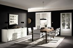 I love this dining room with the natural light and black walls.  I'd have a different table and chairs though.