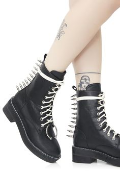 Current Mood Spikestrip Combat Boots will let 'em know they don't wanna come after yew, babe. Stomp 'em out in these sikk combat boots that feature a black vegan leather construction, white lace-up closures, silver ring details on da toez, and a row of spiky silver studs goin' up da back.