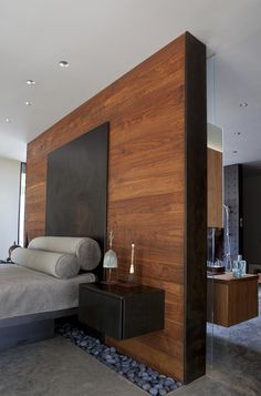 A blackened steel master bed and nightstand float off a walnut-clad wall and over another river rock border. Lighting controls were integrated into the nightstand for a clean look.