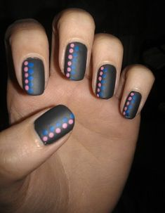 black matte nails with pink and blue dots as accents