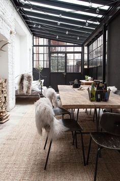 What a wonderful space, very Scandi style with the simple pared back design and neutral colour palette.  Elements to take away: the naturals sisal flooring, the stacked wood pile, the scrubbed wooden table and metal chairs.  Also the sheepskin over the chairs and string lights.  All against a cool backdrop of dark grey doors, windows and grey conservatory roof.