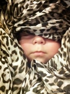 Animal print scarf can be a good frame for a sleeping baby.