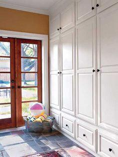 Pass-through Mudroom for Quail Ridge. For the functionality of a mudroom with the look of a simple backdoor, hide everything behind clean white cabinets. Consider organizing the space by family member rather than by item. (Photo: Laurey W. Built In Cabinets, White Cabinets, Diy Cabinets, Mudroom Cabinets, Cupboards, Clean Cabinets, Armoire Entree, Wood Lockers, Wood Doors