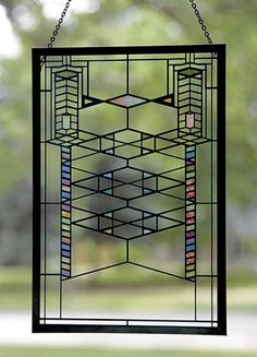 """Robie House Stained Glass This beautiful panel is adapted from one of Wright's twenty-nine distinctive Robie House art glass windows and doors. Painted w/transparent enamels, kiln-fired and framed in a raised copper patina came. Wood stand and hardware for hanging included. 9""""h x 6""""w. $65"""
