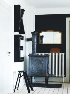 gorgeous vintage stove in a modern space and the wood accents on the black wall are perfect (plus i could easily move right in with my initials on the wall ;)