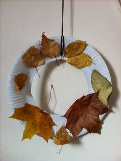 Autumn wreath - paper plate toddler craft. We did this at St Michael's Toddlers, it was a hit. Cut the middle out of a paper plate, tie string/wool for hanging, collect some pretty autumn leaves - give the kids the glue and let them at it! My 2.5 year old did the one pictured. #autumn_crafts_leaves