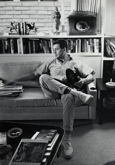Rock Hudson listening to records. Photo by Leo Fuchs