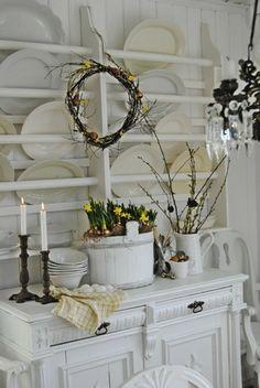 skandinavisch dekorieren zu Ostern offene Regale weißes Porzellan Osterkranz Narzissen im Kübel Frühlingszweige weiße Vase