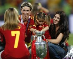 Spain's Fernando Torres, his wife Olalla, right, pose with the trophy for a photograph after Spain won the Euro 2012 soccer championship final  between Spain and Italy in Kiev, Ukraine, Monday, July 2, 2012.