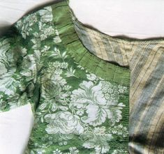 18th century silk garments are often lined with linen. The lining can be striped, checked, printed or plain. Compared to the silk fabric the linen gives a rather rough impression. Caraco, outer fabric silk, around 1750, striped linen lining, silk ribbons, cut 1770-80s,