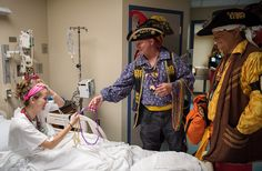 Patient Tori Hamel gets a string of beads from Rick Wolfe and Roy Burnett as pirates from the Ye Mystic Krewe of Gasparilla visit Tampa General Hospital's Children's Medical Center on Tuesday, Jan. 26, 2016