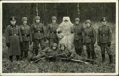 German soldiers pose with a man in a bear costume, 1930's.